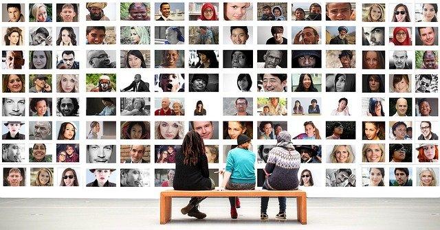 3 personnes qui regardent un mur de photos avec plein de portraits, équipe en construction